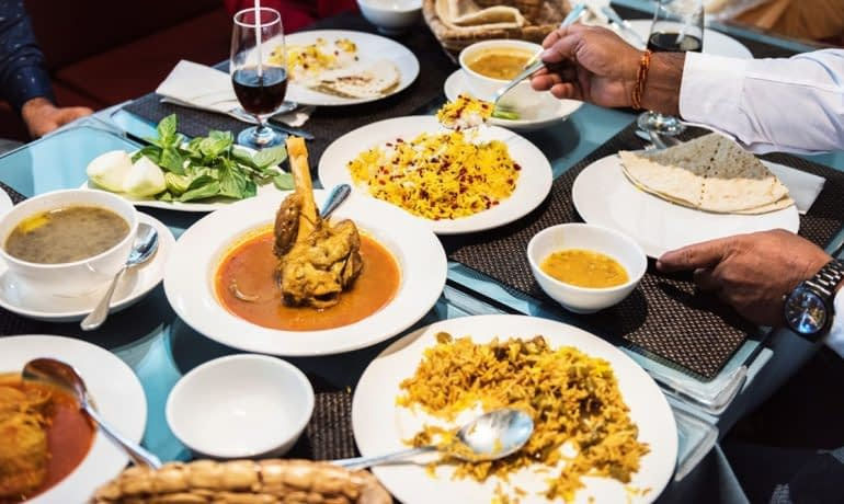 family-having-indian-food-PY9WLXE reduced